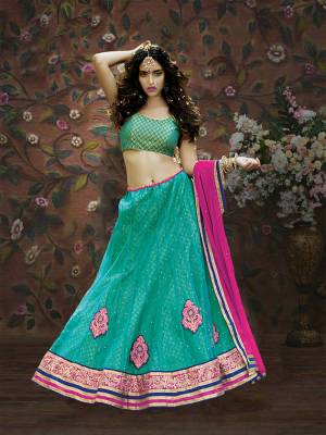 Celebrate This Festive Season With This Pretty Sea Green Colored Lehenga Choli Paired With Rani Pink Colored Dupatta. Its  Brocade Blouse Is Paired With Net And Brocade Fabricated Lehenga With Chiffon Dupatta. Buy Now.