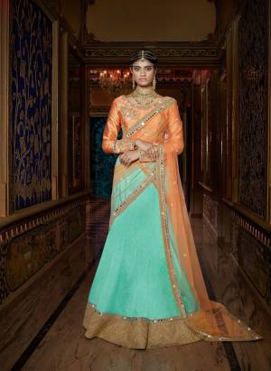 Get Some Unique Colors In Your Ethnic Wear With This Pretty Lehenga Choli. Its Light Orange Colored Choli Is Paired With Aqua Blue Colored Lehenga And Light Orange Colored Dupatta. It Is Beautified With Sophisticated Embroidery Over The Blouse And Dupatta. Buy This Lehenga Choli Now.