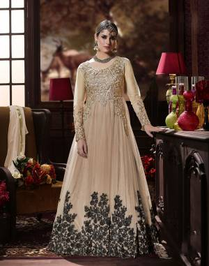 Grab This Beautiful Designer Suit In Beige Color Paired With Beige colored Bottom And Dupatta. Its Top Is Fabricated On Net Paired With Santoon Bottom And Chiffon Dupatta.  This Suit Is Beautified With Black Colored embroidery Over The panel And Golden Embroidered Patch Work. Buy This Suit now.