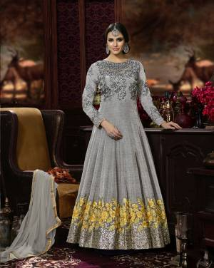 Here Is A Rich And Elegant Looking Floor Length Designer Suit In Grey Color Paired With Grey Colored Bottom And Dupatta. Its Top Is Fabricated On Art Silk Paired With Santoon Bottom And Chiffon Dupatta. It Has Tone To Tone Embroidery And Attractive Embroidery With Contrasting Yellow Color. Buy This Designer Suit Now.