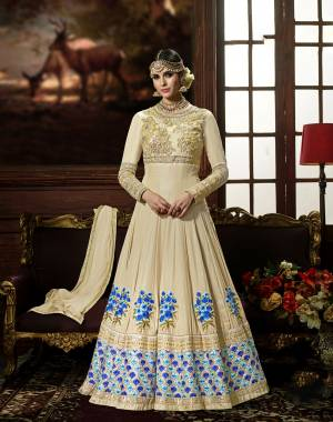 This Wedding Season, Adorn This Lovely Designer Floor Length Suit In Cream Color Paired With Cream Colored Bottom And Dupatta. Its Top Is Fabricated On Crepe Silk Paired With Santoon Bottom And Chiffon Dupatta. It Has Embroidery Yoke And Contrasting Embroidery Over The Panel. Buy Now.