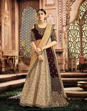 Redefine the legacy of time-honoured styles combined with a modern feel to it in this fusion lehenga in the beautiful shades of Wine And Beige and look magnificent.