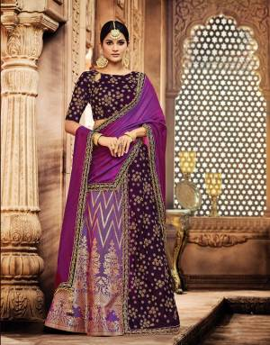 Fabulously feminine and eternally graceful, this royal Wine And Purple Colored lehenga is a sight to behold. Personlify the queenly side of you by adding a maharani style maangtika to your look.