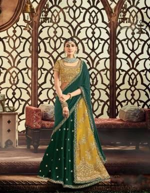 Define your inner empress with utmost panache and flamboyance in this mustard Yellow and Pine green lehenga adorned with gota embroidery.