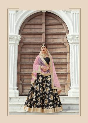 This grand and opulent lehenga set is designed in eye-catching and royal shades of gold and black. It features zari embroidery in flower and leaf motifs all over. The sweetheart neckline blouse giving stunning look to the outfit. It is paired up tith light pink shade dupatta in soft net base.