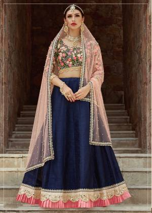 Riot of combination of colors, this bridesmaid lehenga comes in bright navy blue and multi thread color which is truly a bliss. This lehenga is embellished with mirror and dori embroidery on hem with light pink pleats making this lehenga look exquisite. Fabricated with art silk this lehenga is available along with an Dusty Pink pearl work dupatta. Wear it along with some statement jewellary and a pump to complete your bridesmaid look.