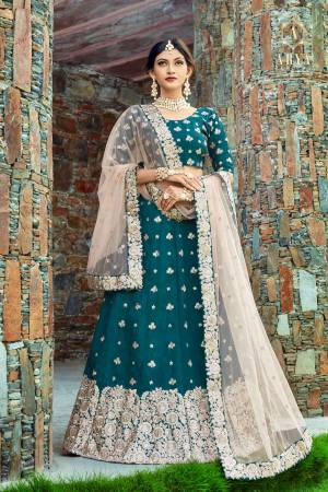 Featuring Teal Blue lehenga set in art silk base. Lehenga is intricated with zari floral motifs further with dori, sequins. It comes with a round neck blouse with zari, sequins and dori embroidery dupatta.