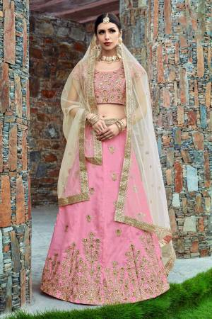Featuring a baby pink blouse in art silk with pearl golden embroidery and it comes along with baby pink lehenga in art silk. It is paired with beige embroidered dupatta in Net.