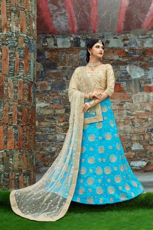 Featuring a Turquoise blue flared lehenga skirt crafted in art silk enhanced with embellished detailing at the bottom. It is paired with a beige blouse in art silk decorated with embroidered motifs. It comes along with a beige dupatta with heavy border.