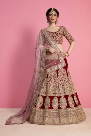 For A Royal Queen Like Look, Grab This Heavy Designer Lehenga Choli In Maroon Color Paired With Light Pink Colored Dupatta. Its Blouse And Lehenga Are Fabricated On Velvet Silk Paired With Net Fabricated Dupatta. Its All Over Heavy Embroidery And Pretty Color Combination Will Earn You Lots Of Compliments From Onlookers.