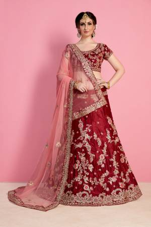 For A Royal Queen Like Look, Grab This Heavy Designer Lehenga Choli In Maroon Color Paired With Light Peach Colored Dupatta. Its Blouse And Lehenga Are Fabricated On Velvet Silk Paired With Net Fabricated Dupatta. Its All Over Heavy Embroidery And Pretty C