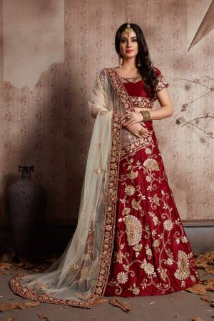 Maroon velvet lehenga with zari embroidery highlighted with topaz crystals paired with a champagne cream dupatta, with a machine embroidered border.