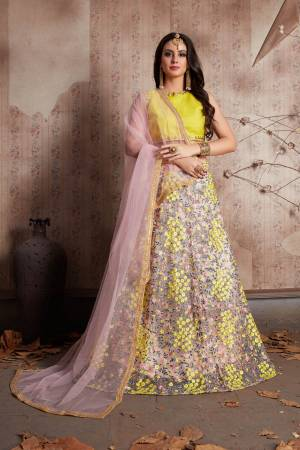Featuring Pastel pink floral motif soft net lehenga . It is paired with yellow round neck,sleeveless art silk base blouse with matching Pastel pink dupatta set.