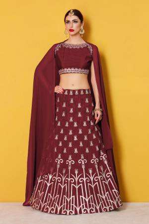 Featuring a maroon blouse in art silk with silver gold embroidery and it comes along with maroon lehenga in art silk. It is paired with maroon plain dupatta in Georgette