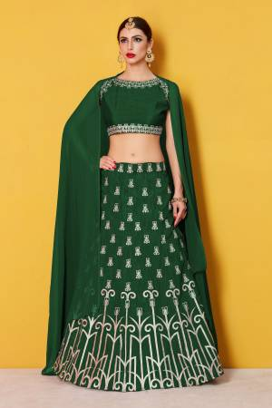 Featuring a Dark green blouse in art silk with silver gold embroidery and it comes along with Dark green lehenga in art silk. It is paired with Dark green plain dupatta in Georgette
