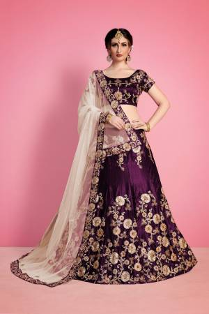 The Purple velvet lehenga blouse set is adorned with all-over floral machine embroidery. It is paired with beige net embroidered dupatta edged with Purple embroidered border.
