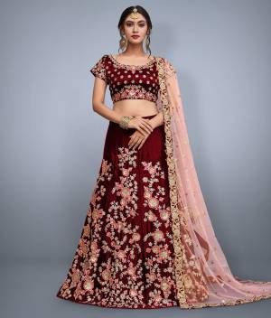 This set features a maroon velvet blouse with golden sequin and floral embroidery on the front and back. It is paired with maroon flared velvet lehenga skirt machine embroidered with gold floral sequin and peach thread work all over the ghera. The lehenga set comes along with Pastel Pink soft net dupatta ornated with over butti and rich embroidered border on all four sides.