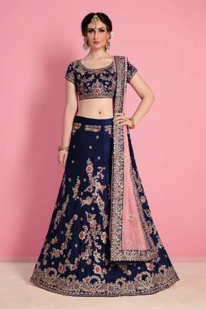 Prefect picture of grace, Bound to fall in love with this elegant yet chic navy blue color silk velvet lehenga choli look featuring dori applique floral work all over lehenga with heavy scattered sequins and stone work on hem completes the look. It comes along with embroidered butta work scattered all around Pastel pink soft net base dupatta.