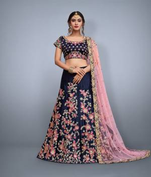 This set features a navy blue velvet blouse with golden sequin and floral embroidery on the front and back. It is paired with blue flared velvet lehenga skirt machine embroidered with gold floral sequin and pink thread work all over the ghera. The lehenga set comes along with peach soft net dupatta ornated with over butti and rich embroidered border on all four sides.