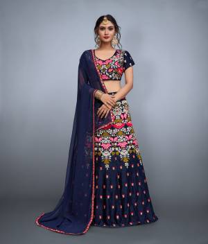 Look no less than any celebrity in this bridesmaids lehenga. The navy blue colored velvet lehenga and choli is enhanced by resham,mirror & zari embroidery in the form of contemporary motifs.