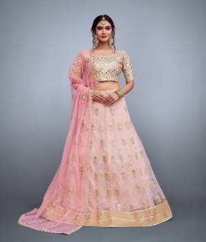 This set features a beige blouse in banglori silk base fully embroidered with mirror, sequins and dori work. It comes along with a baby pink lehenga skirt in soft net with embroidery on ghera and butti flower work scattered all over with zari and mirror work and has an baby pink dupatta in soft net with embroidered flower motifs all over dupatta and floral cutwork lace.