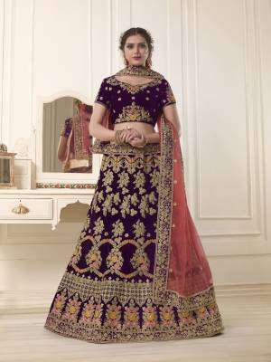 Get Ready for the upcoming wedding season with this very beautiful heavy designer lehenga choli in purple color paired ith contrasting peach colored dupatta. Its blouse and lehenga are fabricated on velvet paired with net fabricated dupatta. It Is Beautified With Heavy Embroidery All Over.