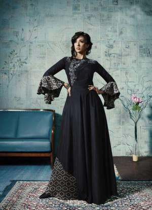 Enhance Your Personality Wearing This Designer Floor Length Gown In Navy Blue Color Fabricated Maslin With Attractive Bell Sleeve Pattern And Embroidery.