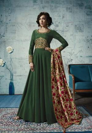 For An Attractive Look, Grab This Designer Readymade Floor Length Gown In Dark Green Color Fabricated On Muslin Paired With Cream Colored Tussar Silk Printed Dupatta. Buy This Now.
