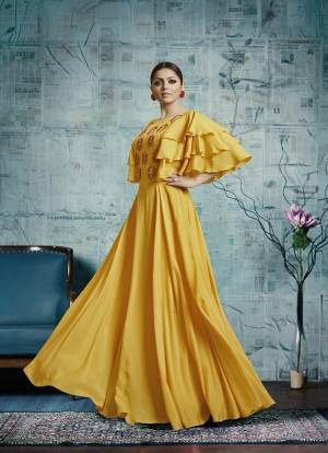 Celebrate This Festive Season Wearing This Designer Floor Length Gown In Yellow Color Fabricated On Maslin Silk. It Is Beautified With Attractive Embroidery Over The Yoke And Frill Patterned Sleeves.