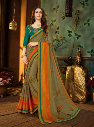 New Color Pallete Is Here With This Saree In Grey And Orange Color Paired With Contrasting Turquoise Blue Colored Blouse. This Saree Is Georgette Fabricated Paired With Art Silk Blouse.