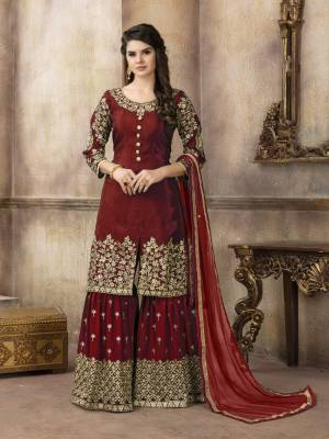 Adorn The Beautiful Royal Look Wearing This Designer Sharara Suit In Maroon Color. Its Top Is Silk Based Paired With Georgette Bottom And Net Dupatta. It Is Beautified With Jari Embroidery And Stone Work .