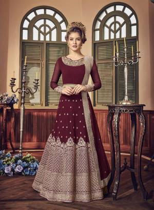 A Must Have Shade In Dark Is Here With This Heavy Designer Floor Length Suit In Maroon Color Paired With Maroon Colored Bottom And Dupatta. Its Long Heavy Top Is Georgette Based Paired With Santoon Bottom And Chiffon Dupatta. It Has Heavy Jari Embroidery Giving A Rich And Elegant Look To The Suit.