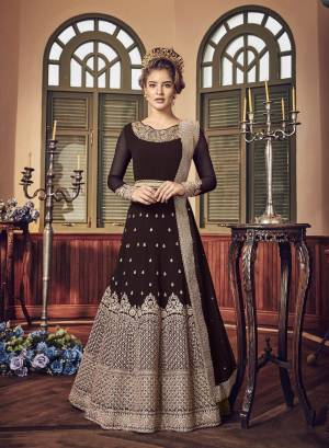 A Must Have Shade In Dark Is Here With This Heavy Designer Floor Length Suit In Dark Brown Color Paired With Dark Brown Colored Bottom And Dupatta. Its Long Heavy Top Is Georgette Based Paired With Santoon Bottom And Chiffon Dupatta. It Has Heavy Jari Embroidery Giving A Rich And Elegant Look To The Suit.