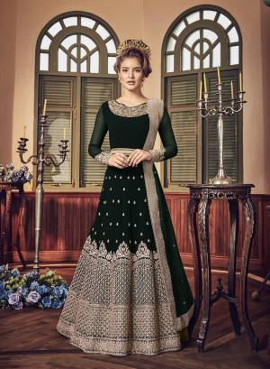 A Must Have Shade In Dark Is Here With This Heavy Designer Floor Length Suit In Dark Wine Green Paired With Dark Green Colored Bottom And Dupatta. Its Long Heavy Top Is Georgette Based Paired With Santoon Bottom And Chiffon Dupatta. It Has Heavy Jari Embroidery Giving A Rich And Elegant Look To The Suit.