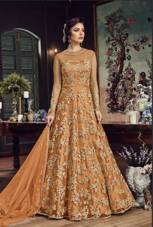Look The Most Prettiest Of All Wearing This Heavy Designer Floor Length Suit In Orange Color Paired With Orange Colored Bottom And Dupatta. Its Top And Dupatta Are Net Fabricated Paired With Santoon Bottom. Buy Now.