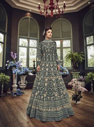 Add This Beautiful Heavy Designer Floor Length Suit In Teal Blue Color Paired With Teal Blue Colored Bottom And dupatta. Its Top And Dupatta Are Net Fabricated Paired With Art Silk Bottom. Also Its Top Is Beautified With Heavy Embroidery All Over.