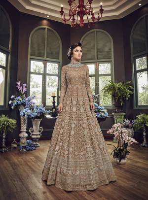 Add This Beautiful Heavy Designer Floor Length Suit In Beige Color Paired With Beige Colored Bottom And dupatta. Its Top And Dupatta Are Net Fabricated Paired With Art Silk Bottom. Also Its Top Is Beautified With Heavy Embroidery All Over.