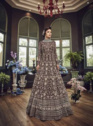 Add This Beautiful Heavy Designer Floor Length Suit In Dark Brown Color Paired With Dark Brown Colored Bottom And dupatta. Its Top And Dupatta Are Net Fabricated Paired With Art Silk Bottom. Also Its Top Is Beautified With Heavy Embroidery All Over.