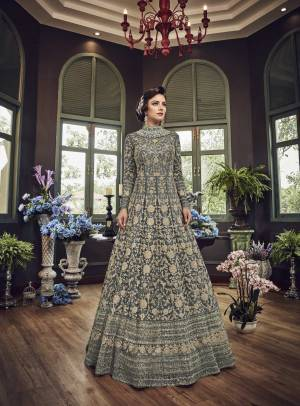 Add This Beautiful Heavy Designer Floor Length Suit In Dark Grey Color Paired With Dark Grey Colored Bottom And dupatta. Its Top And Dupatta Are Net Fabricated Paired With Art Silk Bottom. Also Its Top Is Beautified With Heavy Embroidery All Over.