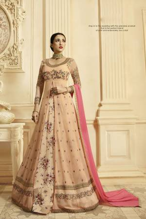 Look The Prettiest Of All Wearing This Designer Floor Length Suit In Light Peach Color Paired With Contrasting Pink Colored Dupatta. It IS Georgette Based With Heavy Embroidery Giving It An Enhanced Look.