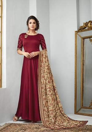 Here Is A Beautiful Designer Floor Length Suit With A Very Royal Color Pallete. Its Top And Bottom Are In Maroon Color Paired With Beige Colored Dupatta. Its Top Is Fabricated On Satin Georgette Paired With Santoon Bottom And Heavy Embroidered Art Silk Dupatta. Buy Now.