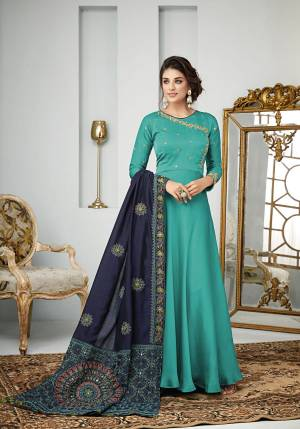 Add This Designer Floor Length Suit In Shades Of Blue To Your Wardrobe. Its Top and Bottom Are In Turquoise Blue Color Paired With Navy Blue Colored Dupatta, Its Top Is Fabricated On Satin Georgette Paired With Santoon Bottom And Art Silk Dupatta.