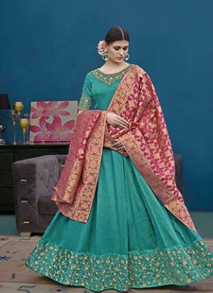 For This Wedding And Festive Season, Grab This Designer Floor Length Suit In Turquoise Blue Color Paired With Contrasting Pink Colored Dupatta. Its Top Is Fabricated On Art Silk Paired With Santoon Bottom And Banarasi Jacquard Dupatta. Buy Now.