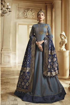 Rich And Elegant Looking Designer Floor Length Suit Is Here In Grey Color Paired With Contrasting Navy Blue Colored Dupatta. Its Top IS Soft Silk Based Paired With Santoon Bottom And Banarasi Art Silk Fabricated Dupatta. It Has Very Rich Color Pallete Which Will Earn You Lots Of Compliments From Onlookers.