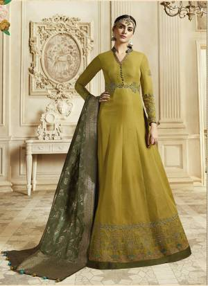 Celebrate This Festive And Wedding Season Wearing This Designer Floor Length Suit In Musturd Yellow Color Paired With Contrasting Olive Green Colored Dupatta. Its Top Is Fabricated On Soft Silk Paired With Santoon Bottom And Banarasi Art Silk Dupatta. Buy Now.