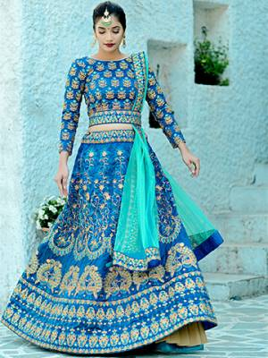 Another Beautiful Designer Heavy Lehenga Choli Is Here In Blue Color Paired With Contrasting Sea Green Colored Dupatta. Its Blouse And Lehenga Are Fabricated On Art Silk Paired With Net Fabricated Dupatta. Buy This Now.