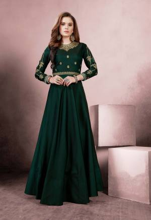 Celebrate This Festive Season Wearing This Designer Floor Length Readymade Gown In Dark Green Color Fabricated On Tafeta Silk. It Is Beautified With Heavy Embroidery Over The Yoke And Sleeves.