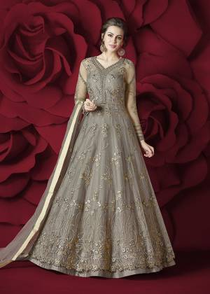 Flaunt Your Rich and Elegant Taste Wearing This Designer Floor Length Suit In Grey Colored Top Paired With Grey Colored Bottom And Dupatta. Its Top Is Fabricated On Net Paired With Silk Bottom And Net Dupatta. Its Rich and Elegant Embroidery Will Earn Your Lots Of Compliments From Onlookers.