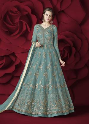 Flaunt Your Rich and Elegant Taste Wearing This Designer Floor Length Suit In Turquoise Blue Colored Top Paired With Turquoise Blue Colored Bottom And Dupatta. Its Top Is Fabricated On Net Paired With Silk Bottom And Net Dupatta. Its Rich and Elegant Embroidery Will Earn Your Lots Of Compliments From Onlookers.