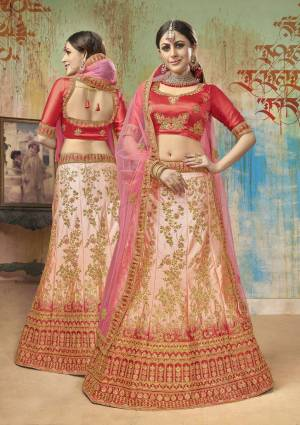 Shine Bright Wearing This Heavy Designer Lehenga Choli In Red Colored Blouse Paired With Light Peach Lehenga And Pink Colored Dupatta. Its Blouse And Lehenga Are Satin Silk Based Paired With Net Fabricated Dupatta. It Is Beautified With Heavy Embroidery All Over.